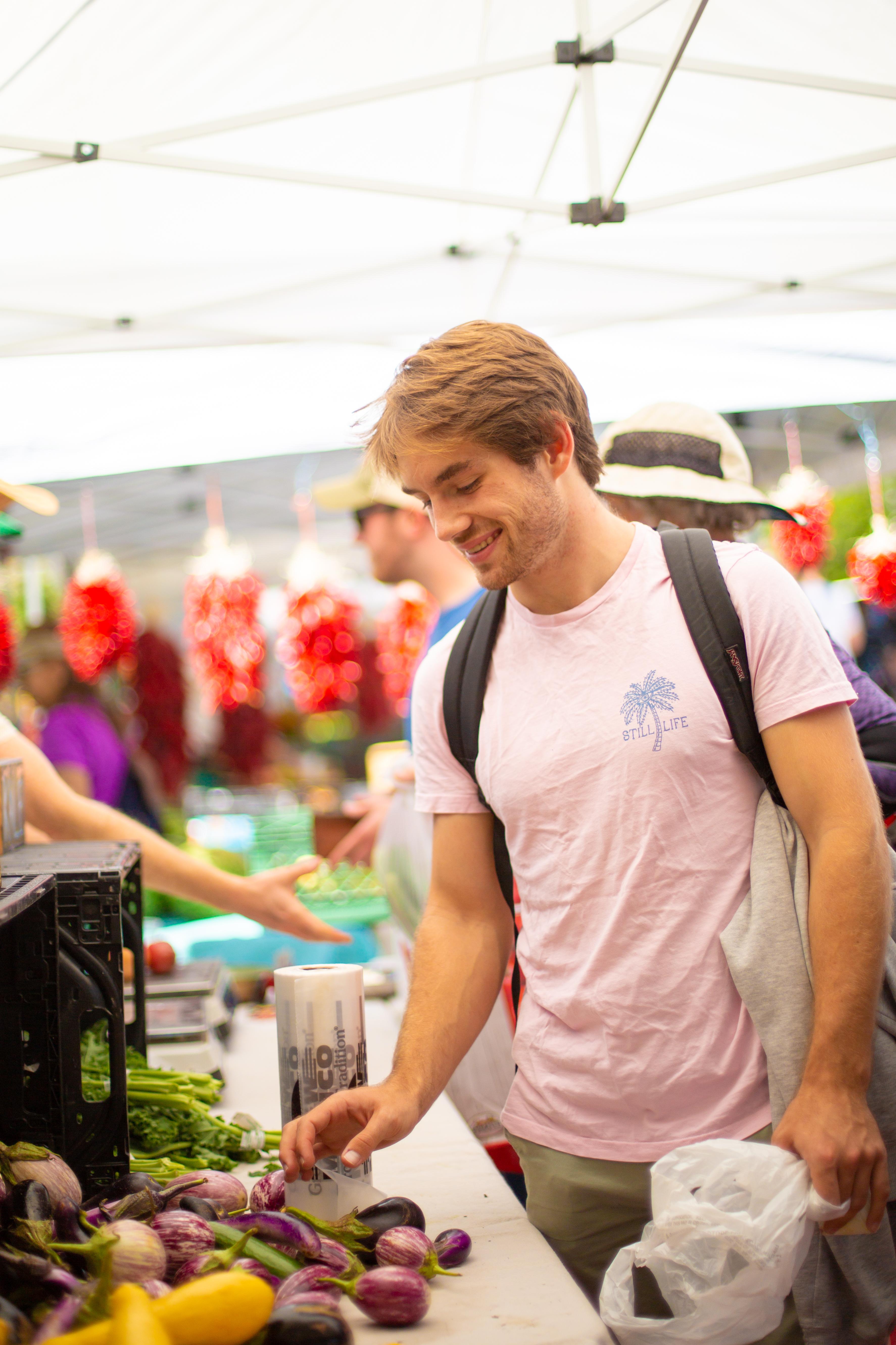 男子在农贸市场采摘水果。