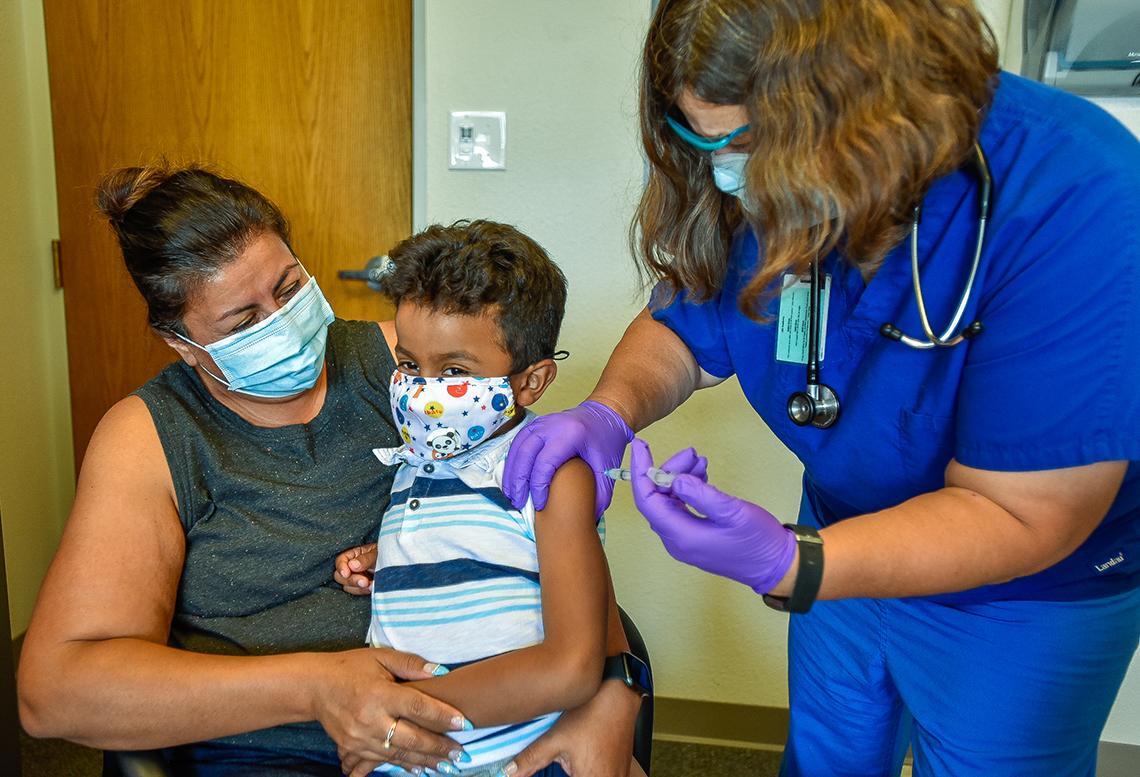Mamá con hijo recibiendo la vacuna