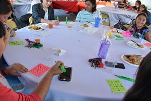 Estudiantes jugando al bingo alrededor de una mesa.