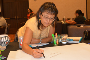 Woman writing at table during CHAW.
