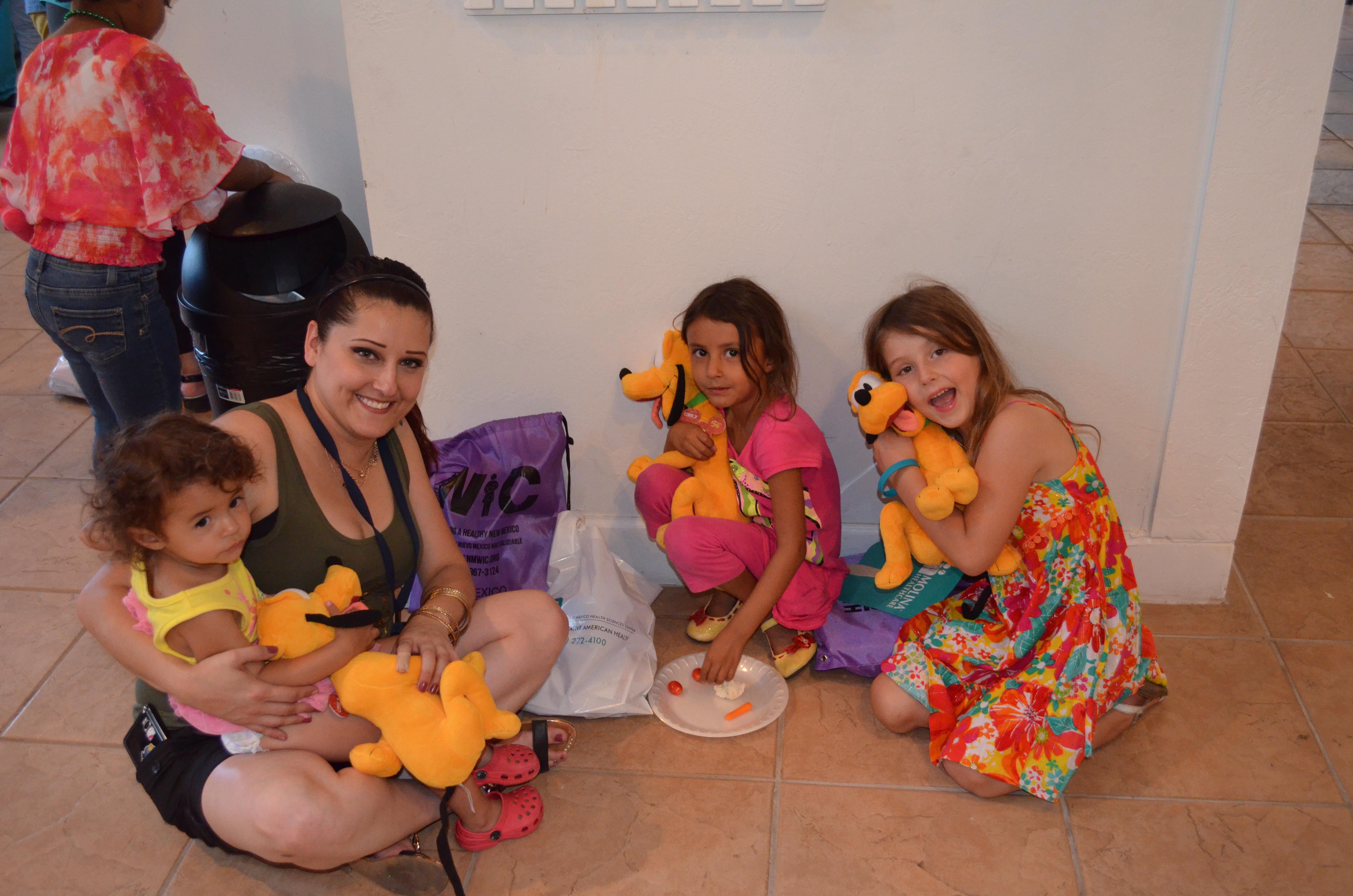 Mama mit drei Mädchen. Jedes Mädchen hält einen ausgestopften Pluto.