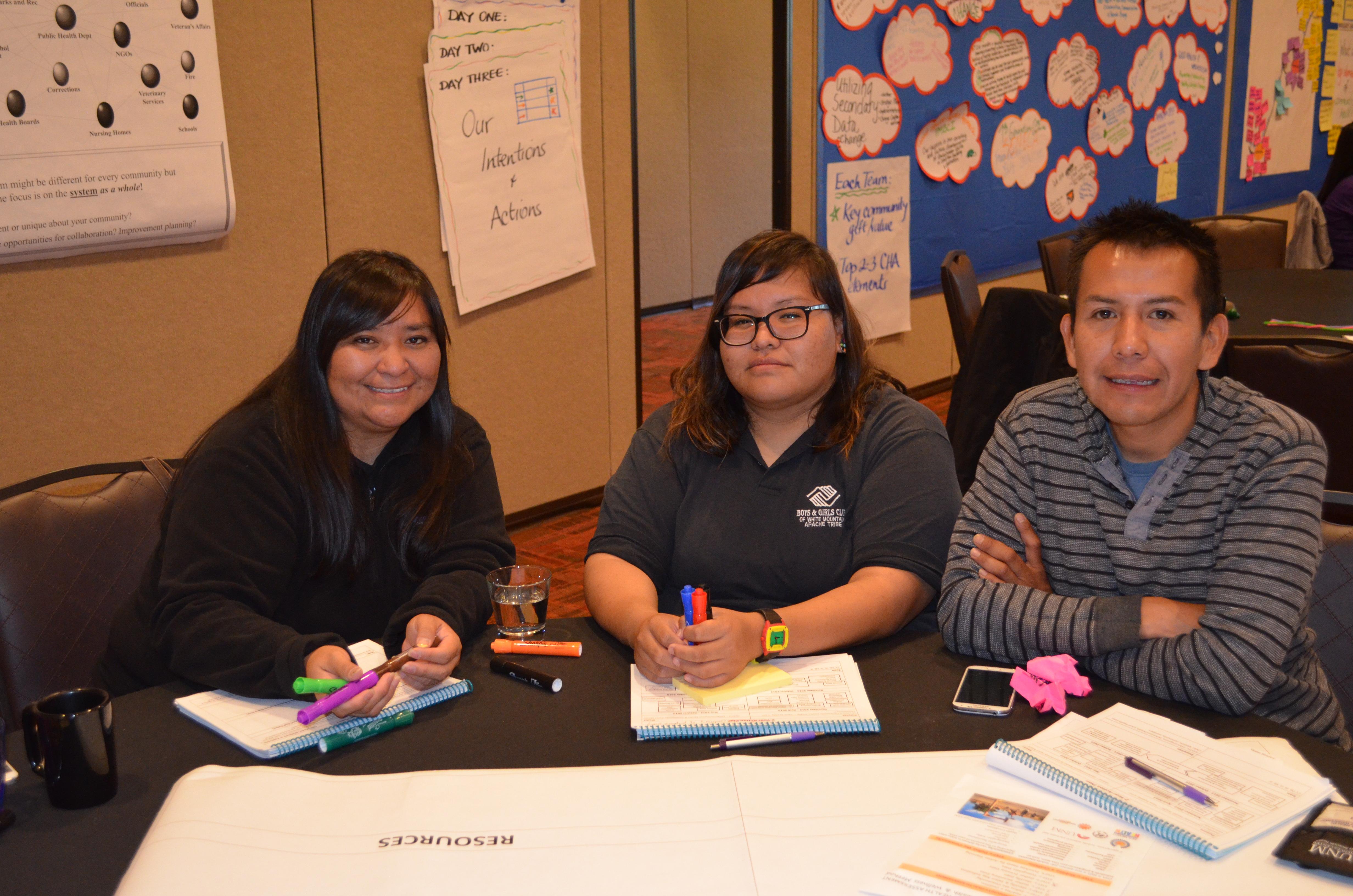 Foto de grupo de tres sentados a la mesa.