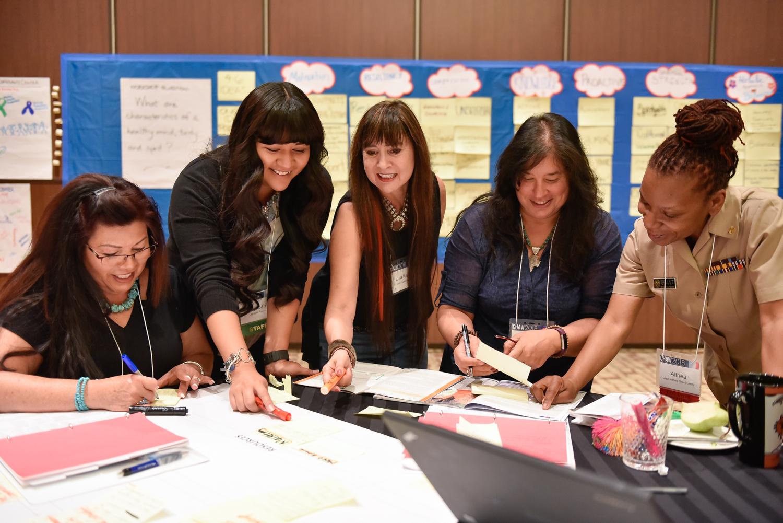 קבוצה מחייכת ועובדת ליד השולחן.