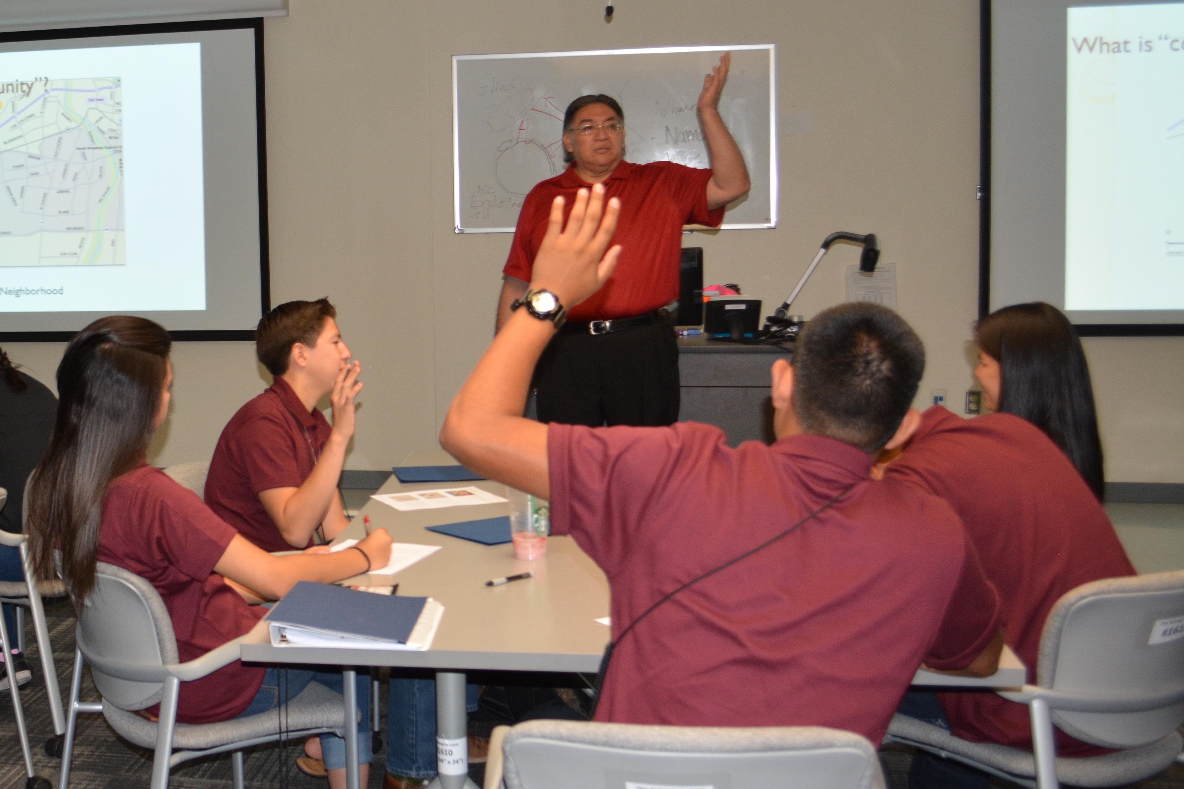 Norman Cooeyate présente, des étudiants assis à des tables levant la main.