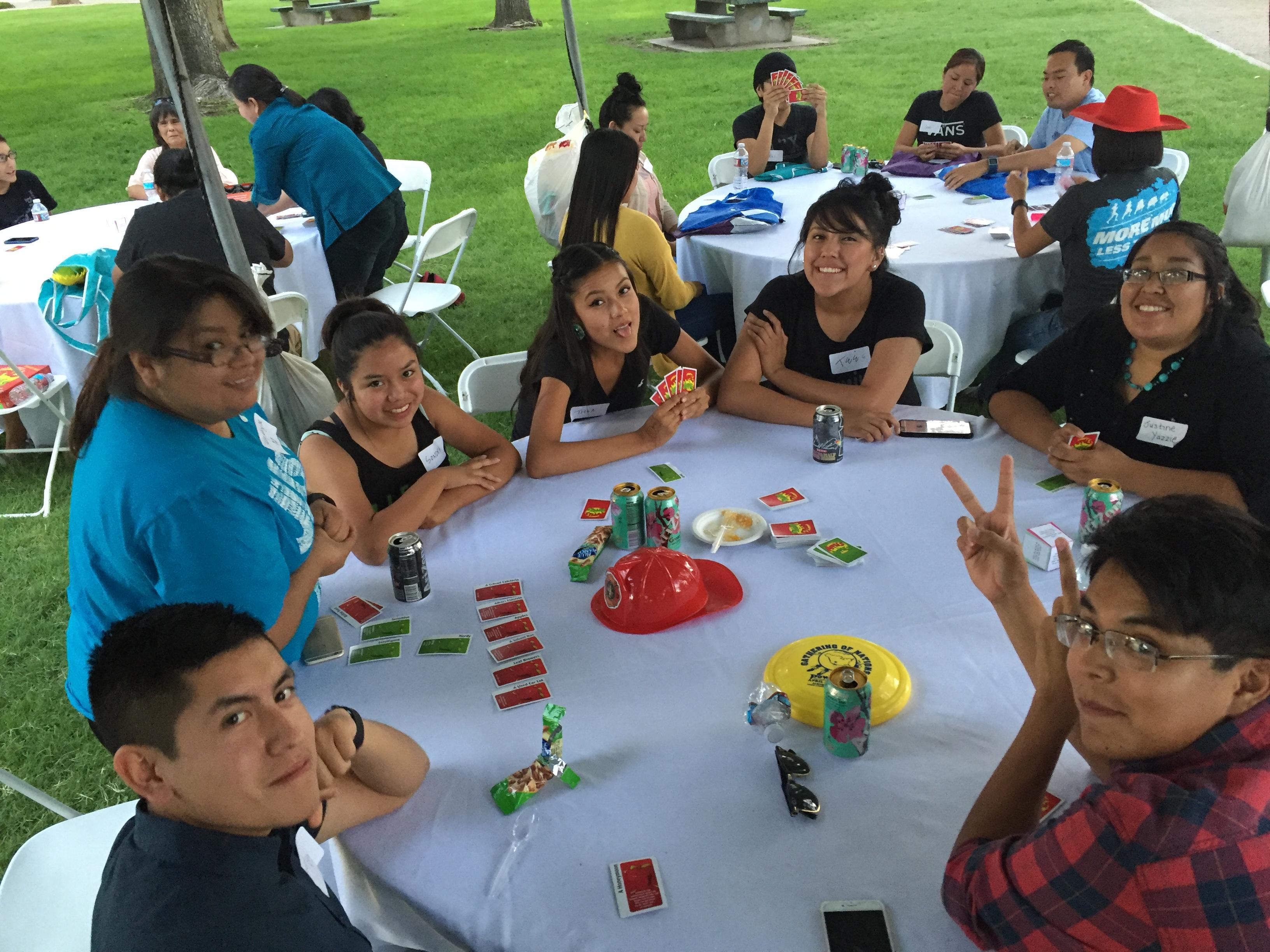 Groupe assis à table à l'extérieur jouant des pommes aux pommes.