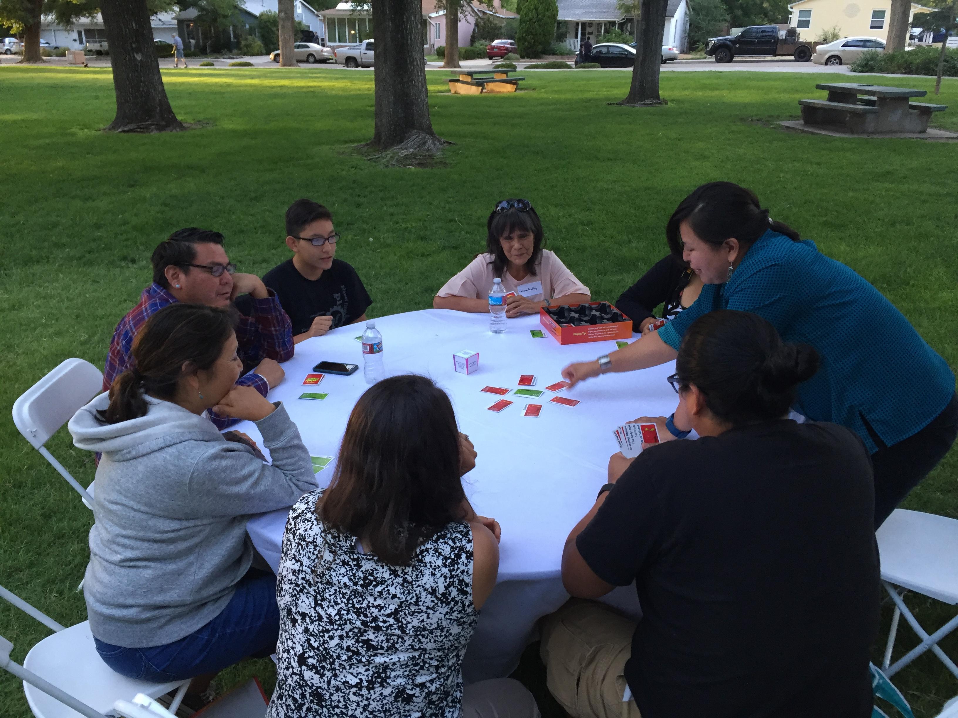 Groupe jouant des pommes aux pommes à table à l'extérieur.