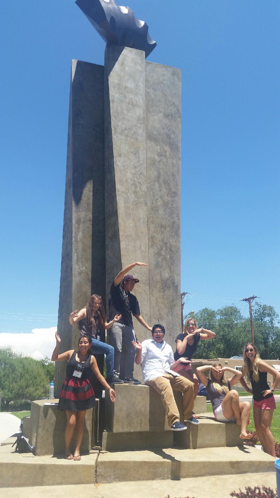 Étudiants posant à la base de la sculpture.