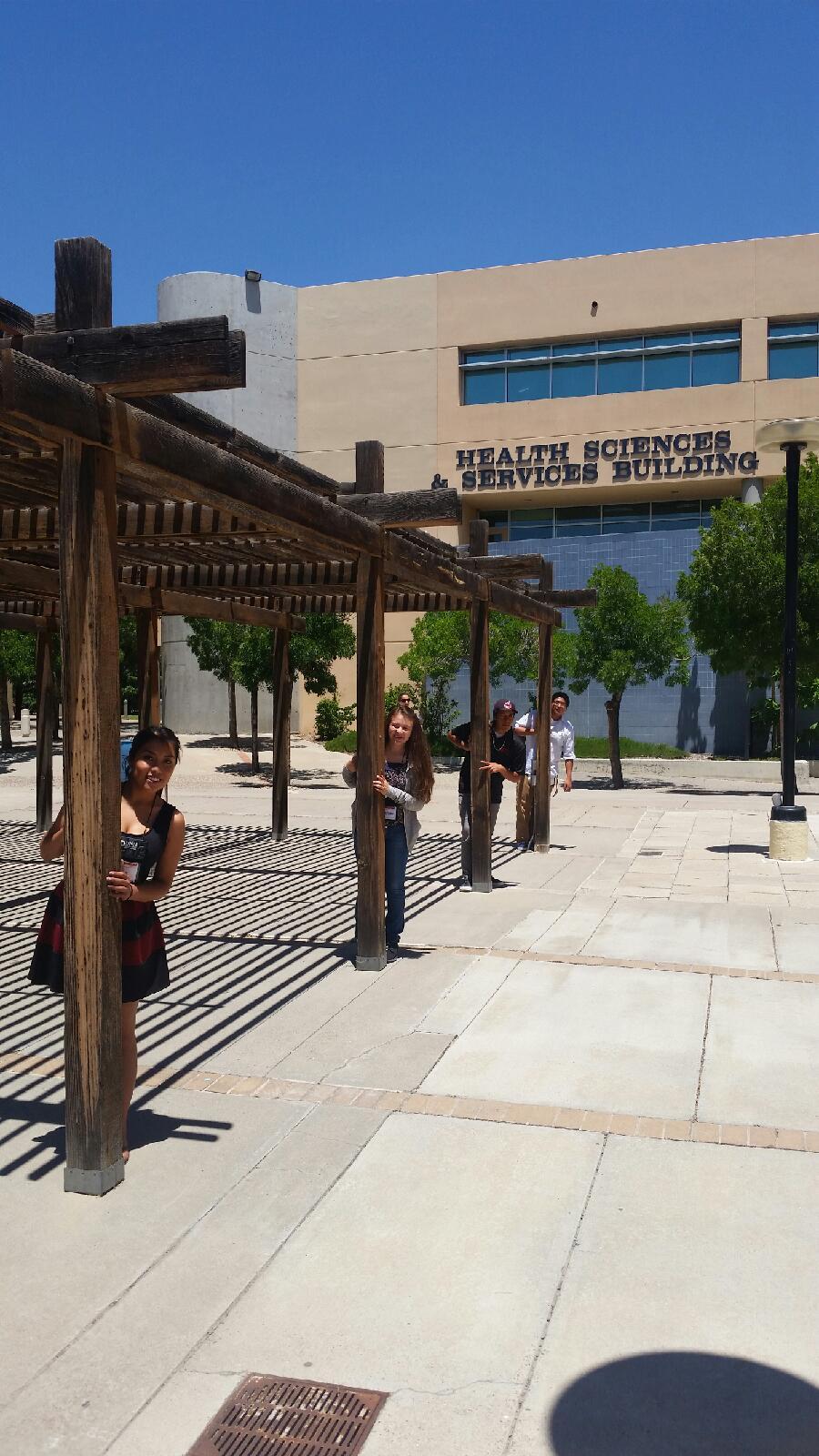 Étudiants posant devant des poteaux depuis le bâtiment HS&S.