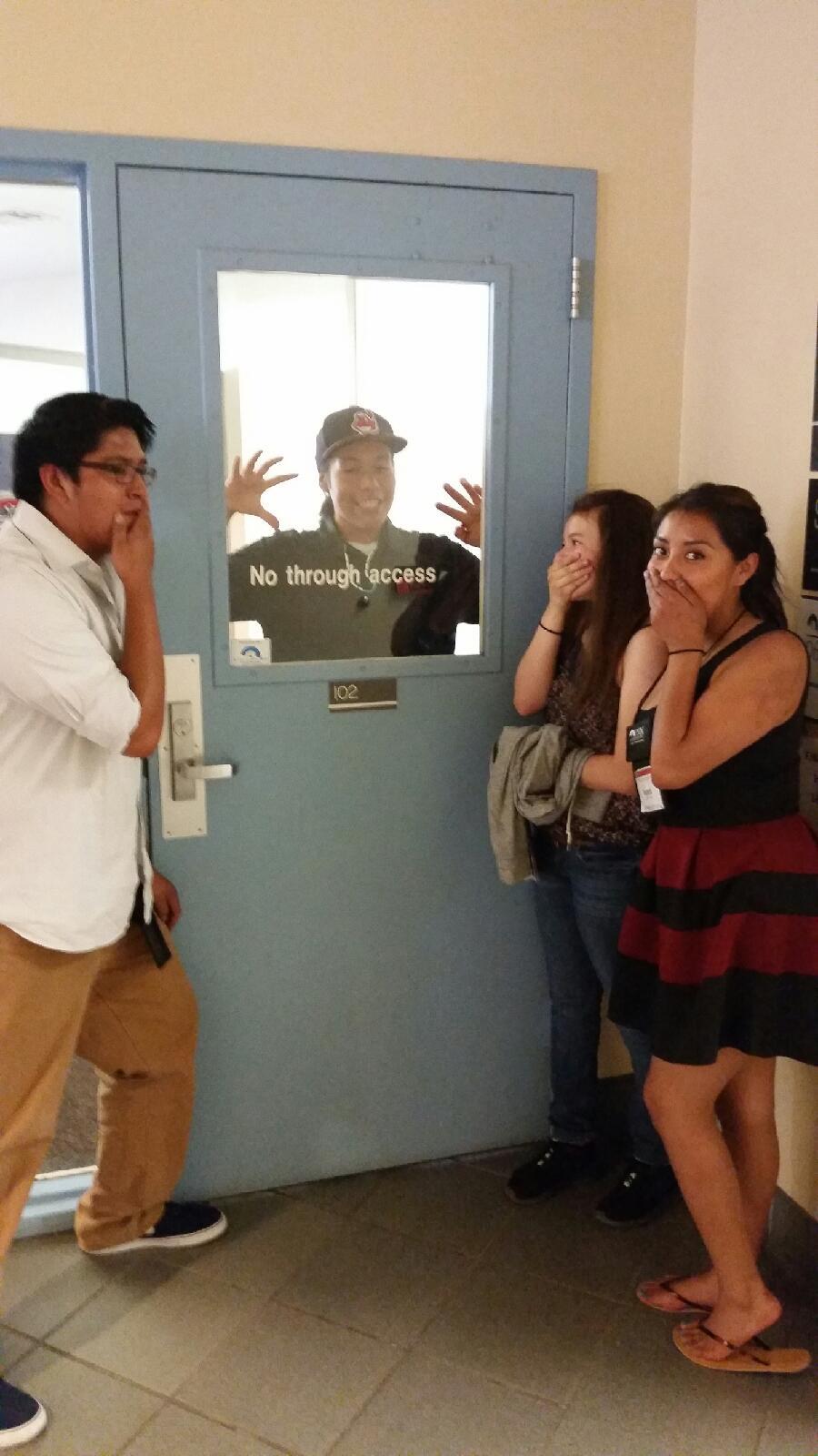 Étudiant posant à l'extérieur de la porte d'accès sans issue - un étudiant prétendant être piégé à l'intérieur.