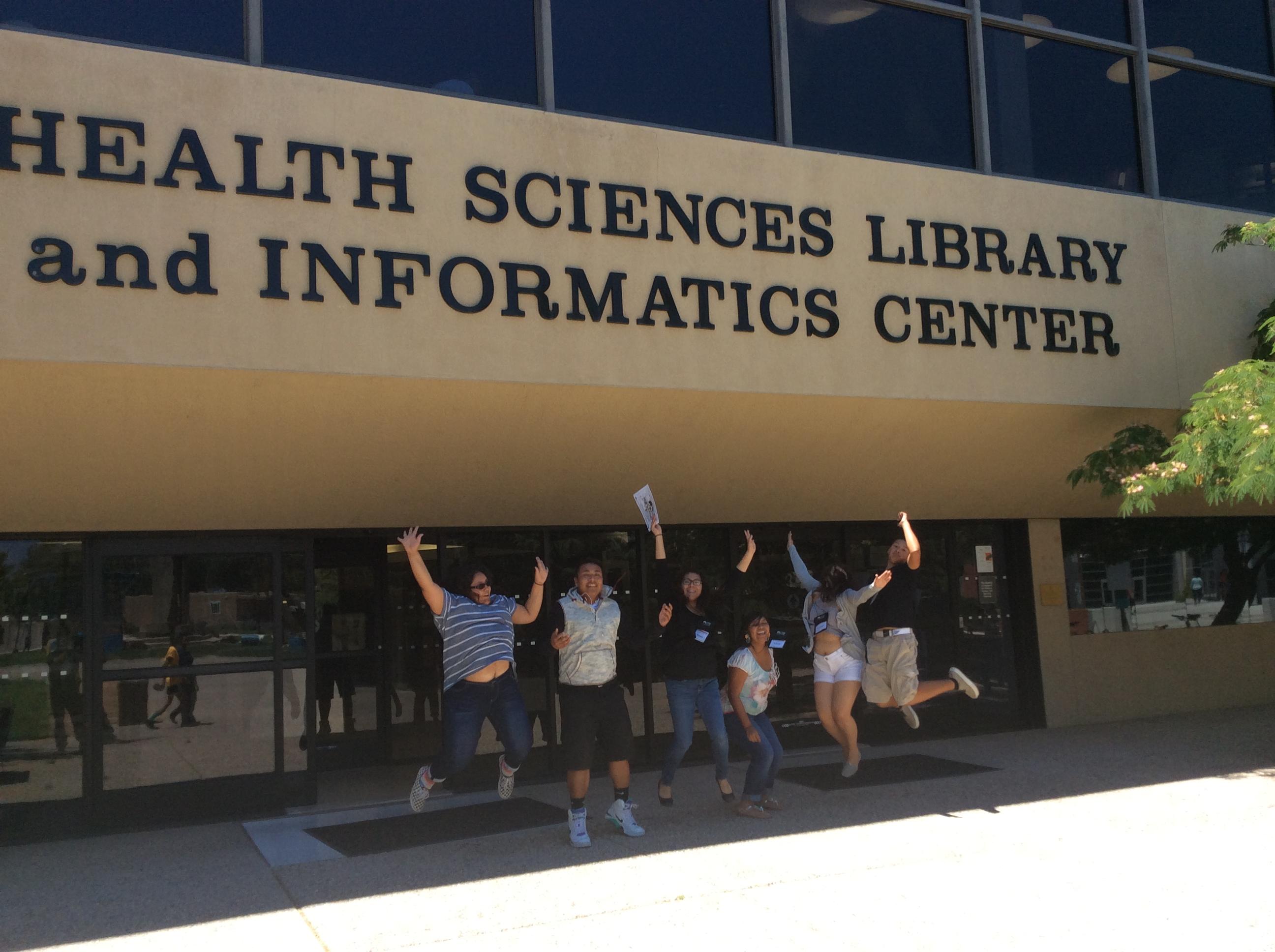 Étudiant sautant devant la bibliothèque.