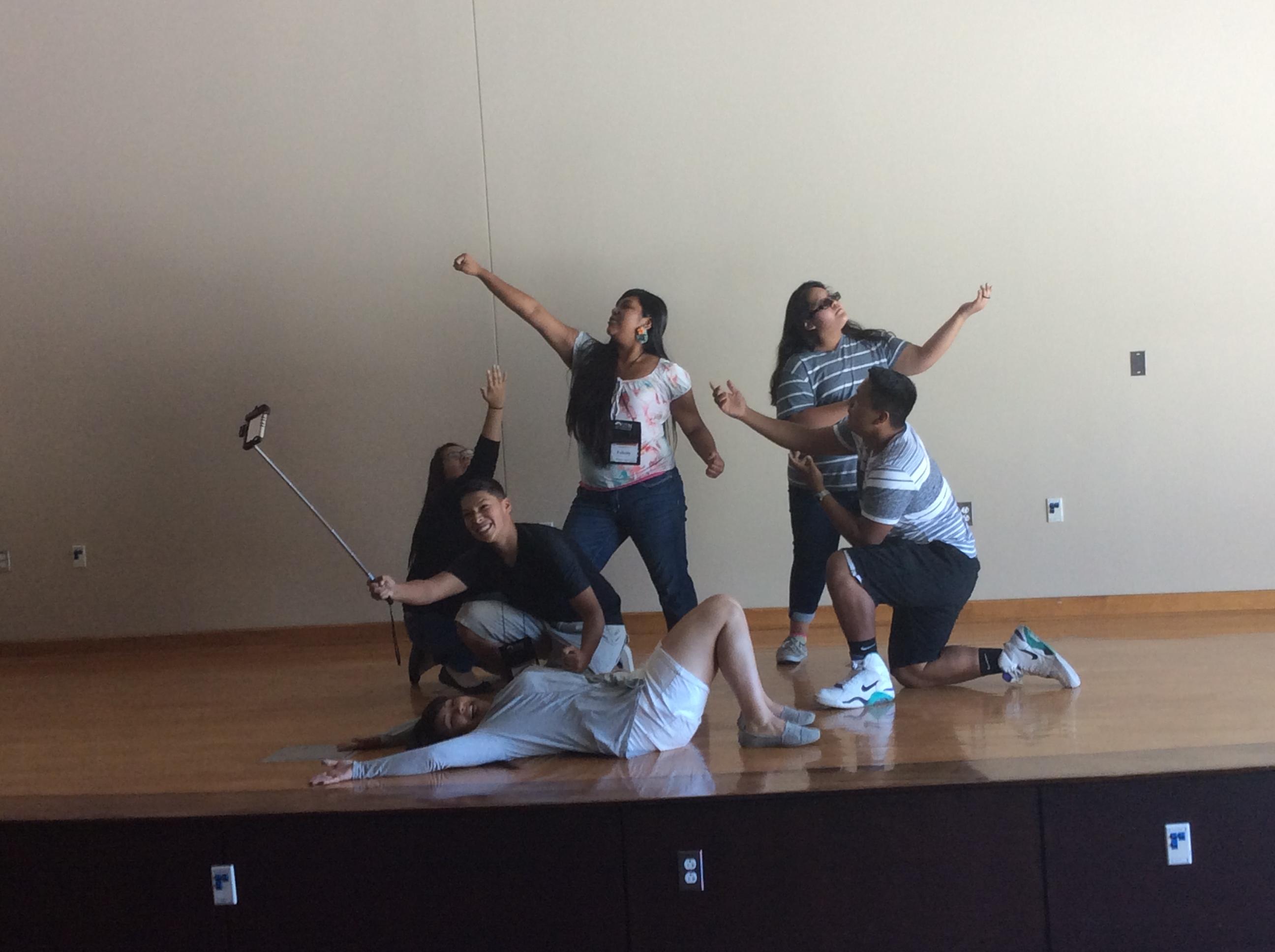 Des étudiants posant sur scène dans des poses de danse dramatique.