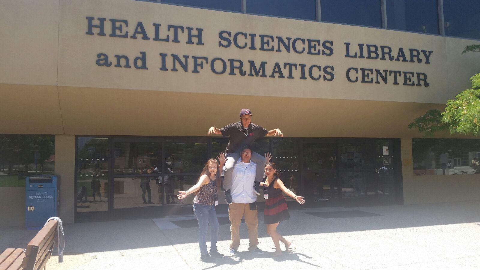 Étudiants posant devant la bibliothèque HS et le centre d'information.