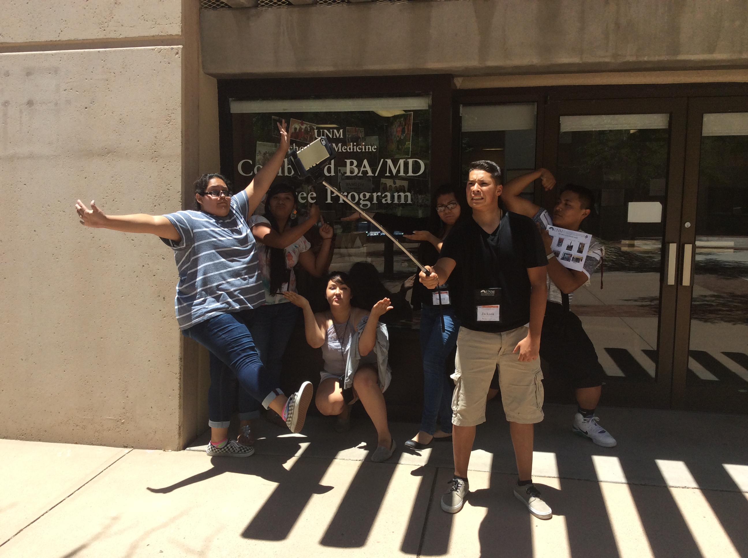 Étudiants posant avec selfie-cam devant les portes du bureau.