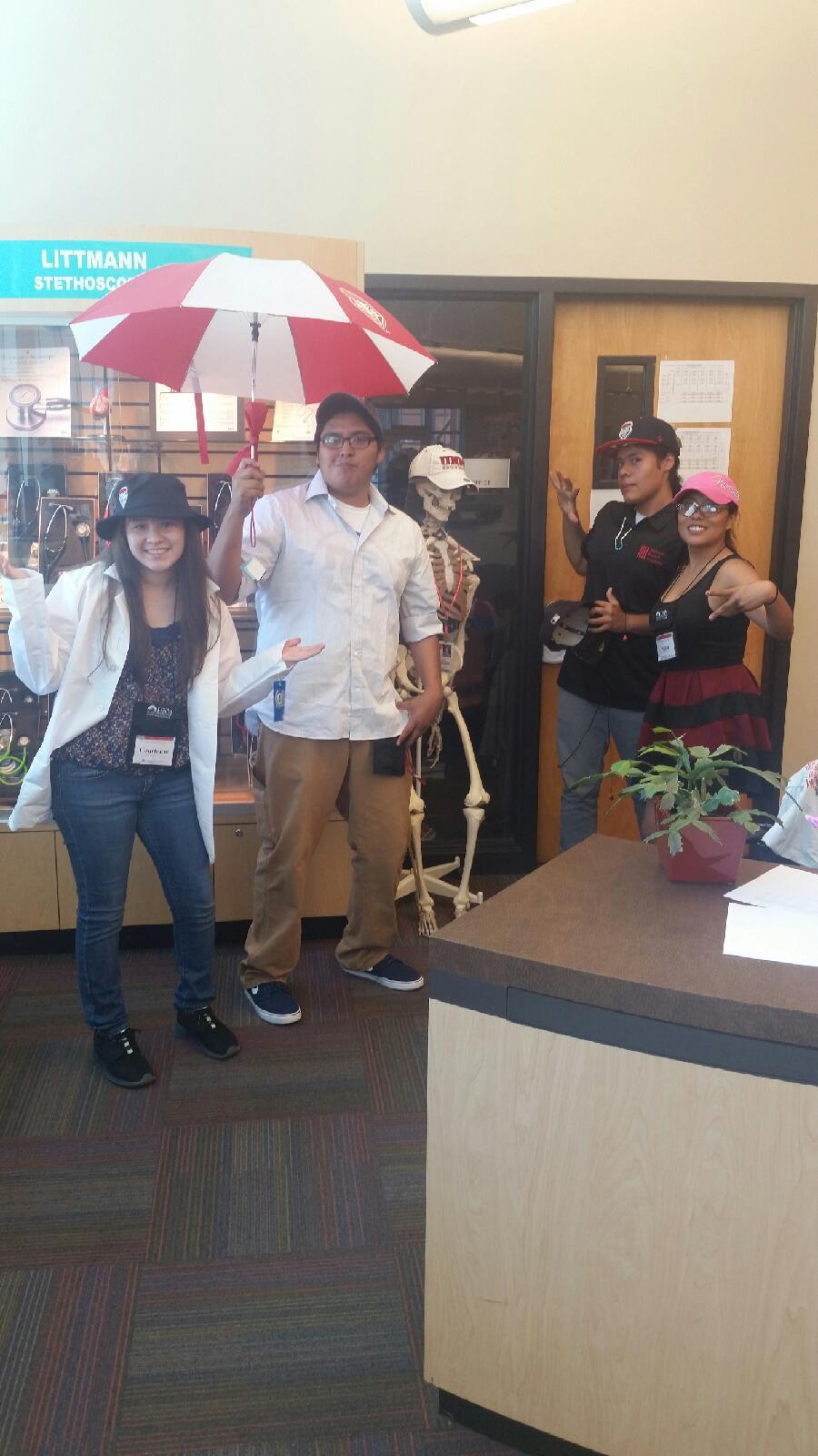 Étudiants debout à l'intérieur, posant avec un parapluie.