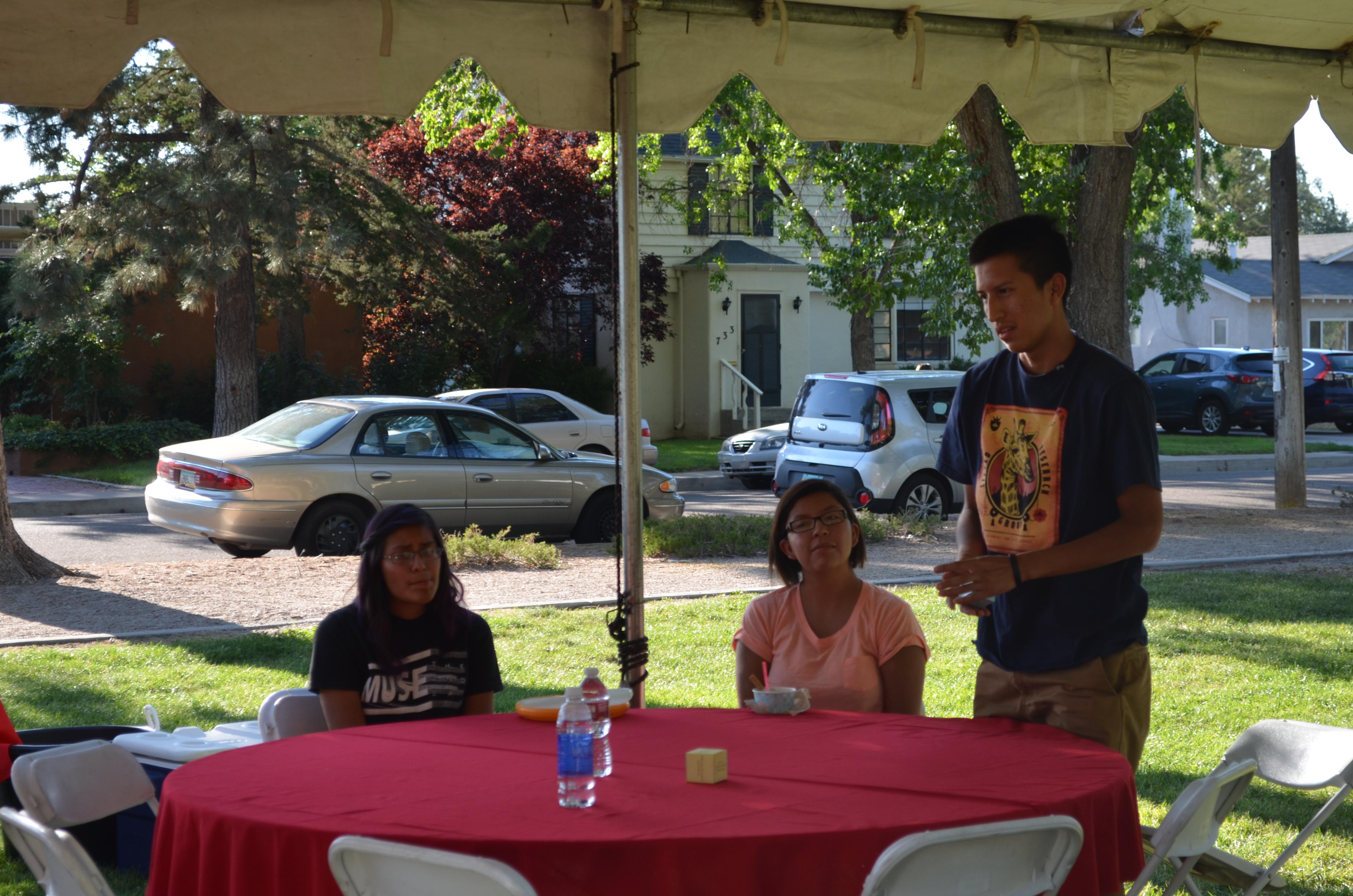 Des élèves assis autour de tables à l'extérieur.