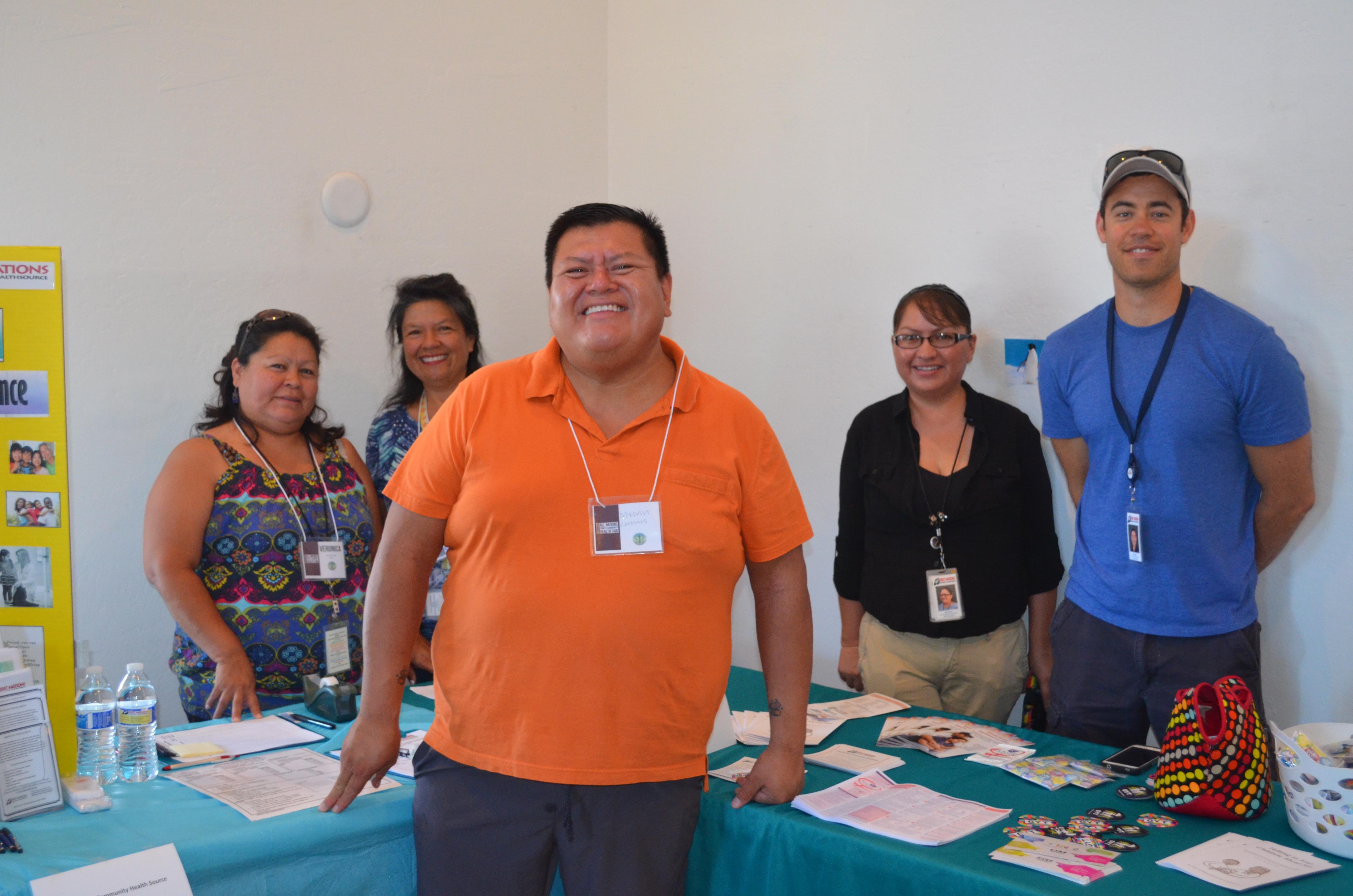 Melvin, Veronica und andere Freiwillige stehen am Tisch.