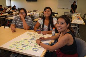 Studente sorridente mentre lavora al tavolo.
