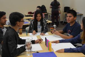 Estudiantes que trabajan en la mesa.