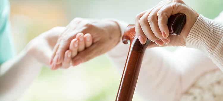 Anciano con un bastón en una mano, sosteniendo la mano de alguien con la otra.