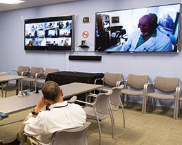 Un hombre se sienta frente a dos pantallas con teleECHO en sesión,