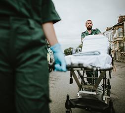 Foto de técnicos de emergencias médicas con paciente en camilla.