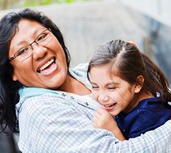 Foto de una mujer india americana feliz con un niño en sus brazos.