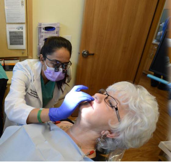 Residente examinando la boca del paciente.