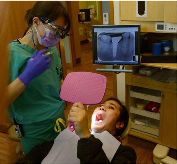 Paciente mirando su boca en un espejo de mano después del procedimiento.
