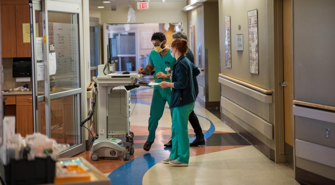 Dois membros da equipe em pé no corredor da UTI Neuro.