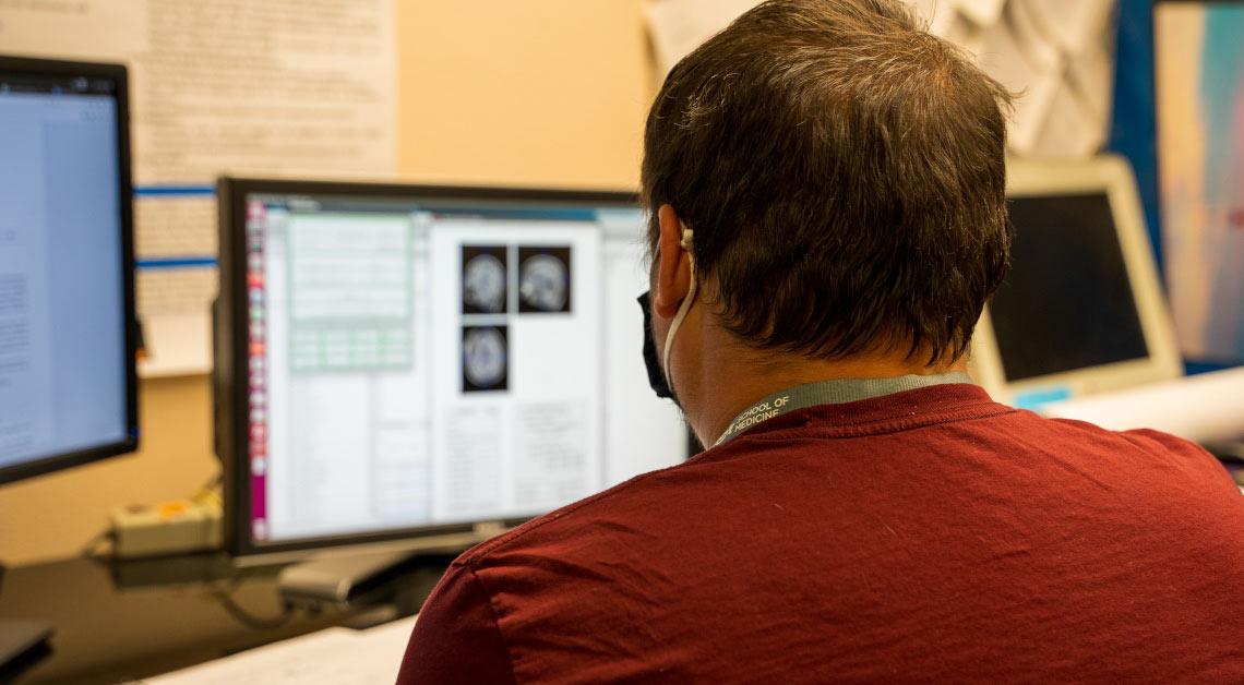 Membro do laboratório olhando para o computador.