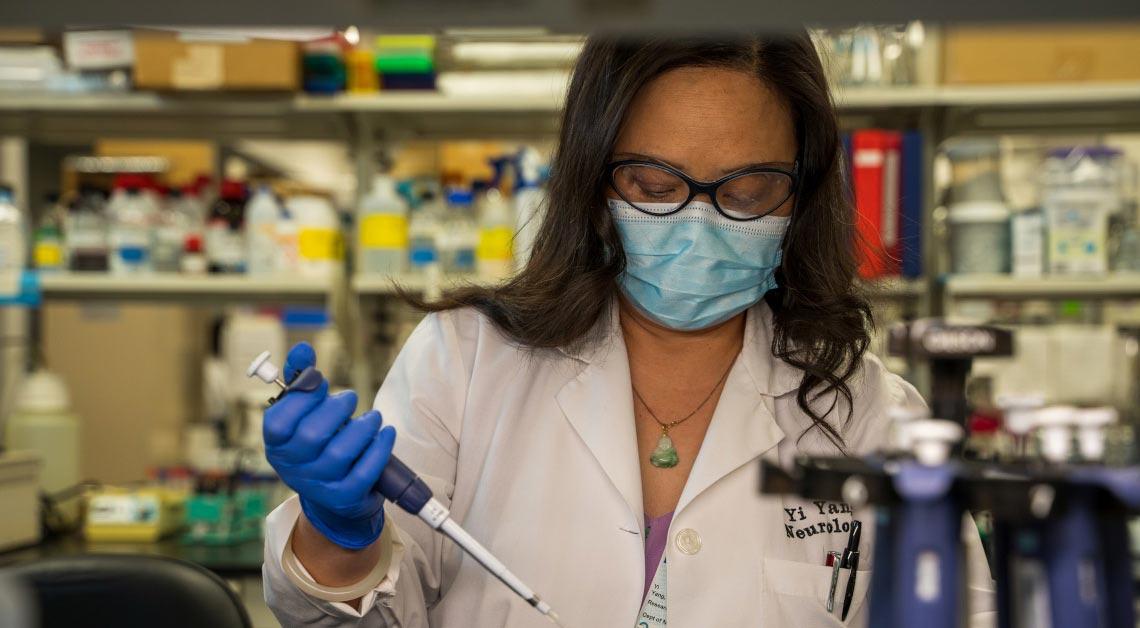 Yi Yang usando pipeta no laboratório.