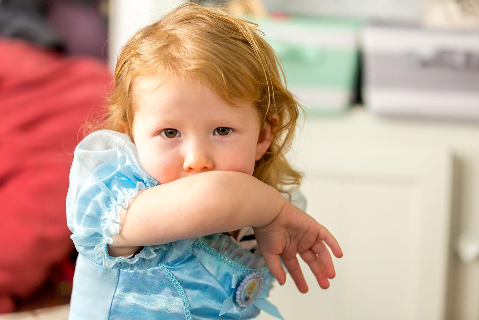 Un niño pequeño tosiendo en su brazo.