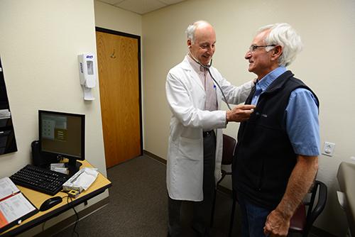 Un médico sosteniendo un estetoscopio en el pecho de un paciente.
