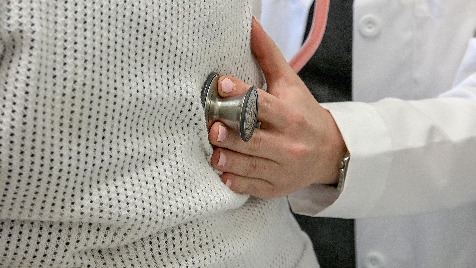 Un médico sosteniendo un estetoscopio en el vientre de una mujer embarazada