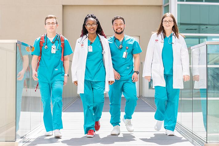 Cuatro estudiantes afuera caminando