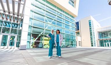 Dos estudiantes de enfermería de pie fuera del edificio.