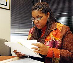 Mujer leyendo papeles en el escritorio.