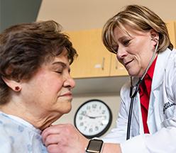Enfermera practicante escuchando el corazón de la mujer madura.