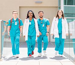 Estudiante de enfermería caminando con orgullo.