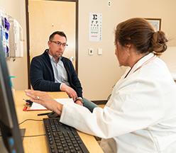 Enfermera practicante en computadora hablando con un hombre.