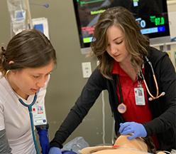 Estudiantes practicando en paciente de simulación.