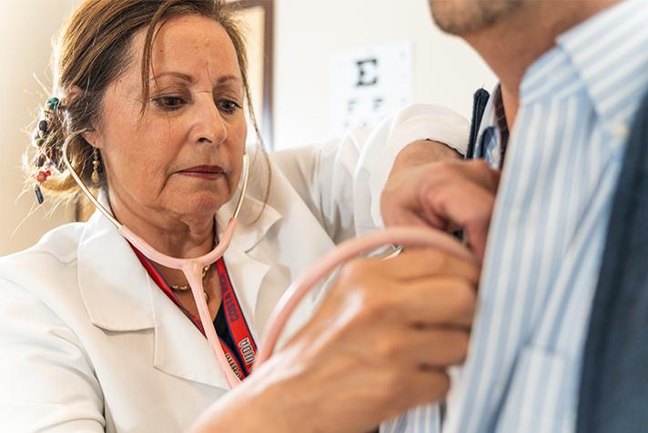 Enfermera escuchando el corazón del hombre con estetoscopio.