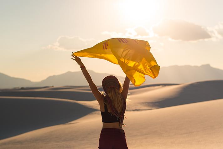Femmina in dune di sabbia con bandiera NM
