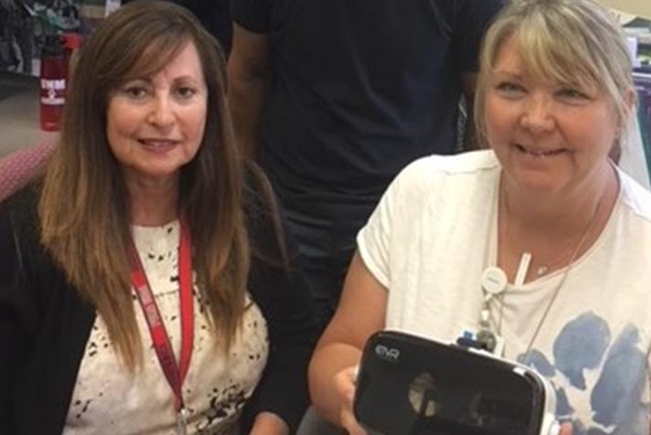 2 mujeres miembros de la facultad sostienen gafas de realidad virtual