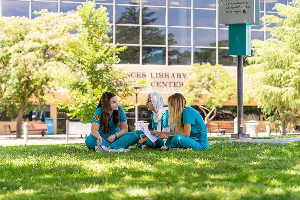 3 estudiantes de enfermería que estudian sobre césped.