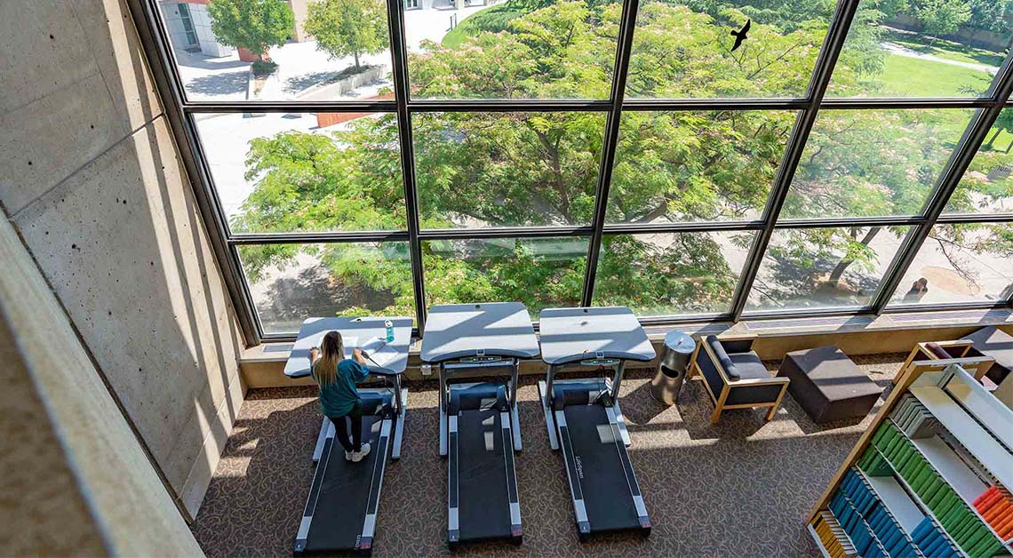 student on treadmill in library