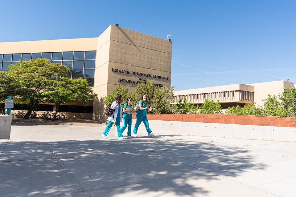 Estudiantes caminando cerca del frente de la biblioteca de HSC.