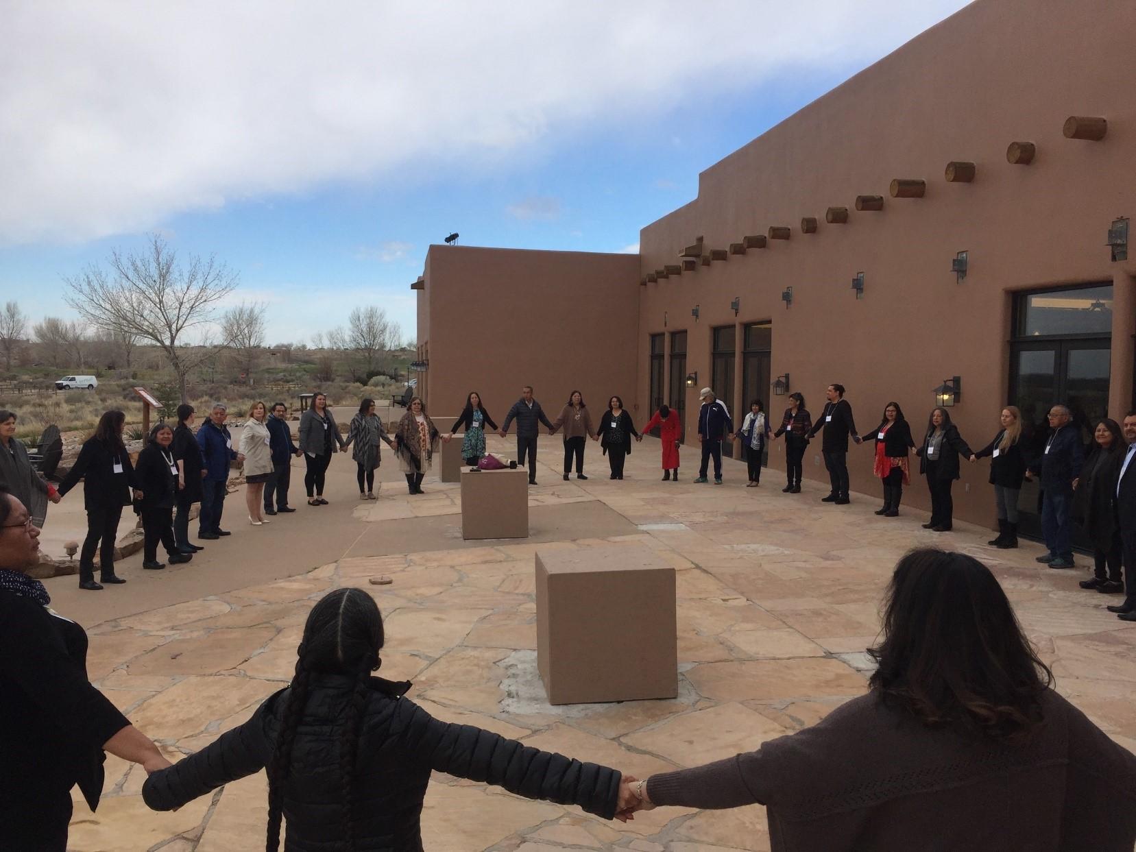 Miembros del Centro TREE parados afuera tomados de la mano en círculo