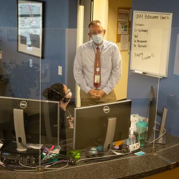 Christopher Morris de pie detrás del mostrador de facturación hablando con los recepcionistas de la recepción.