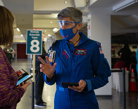 Trabajador de la salud hablando con la mujer y dirigiendo el flujo del tráfico.